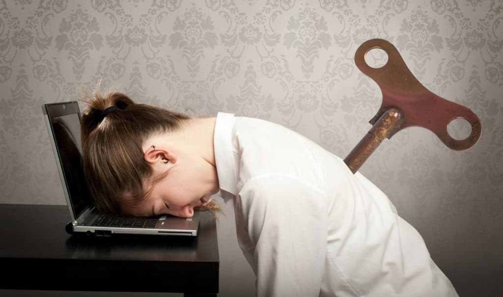 Overworked woman asleep with her head on laptop