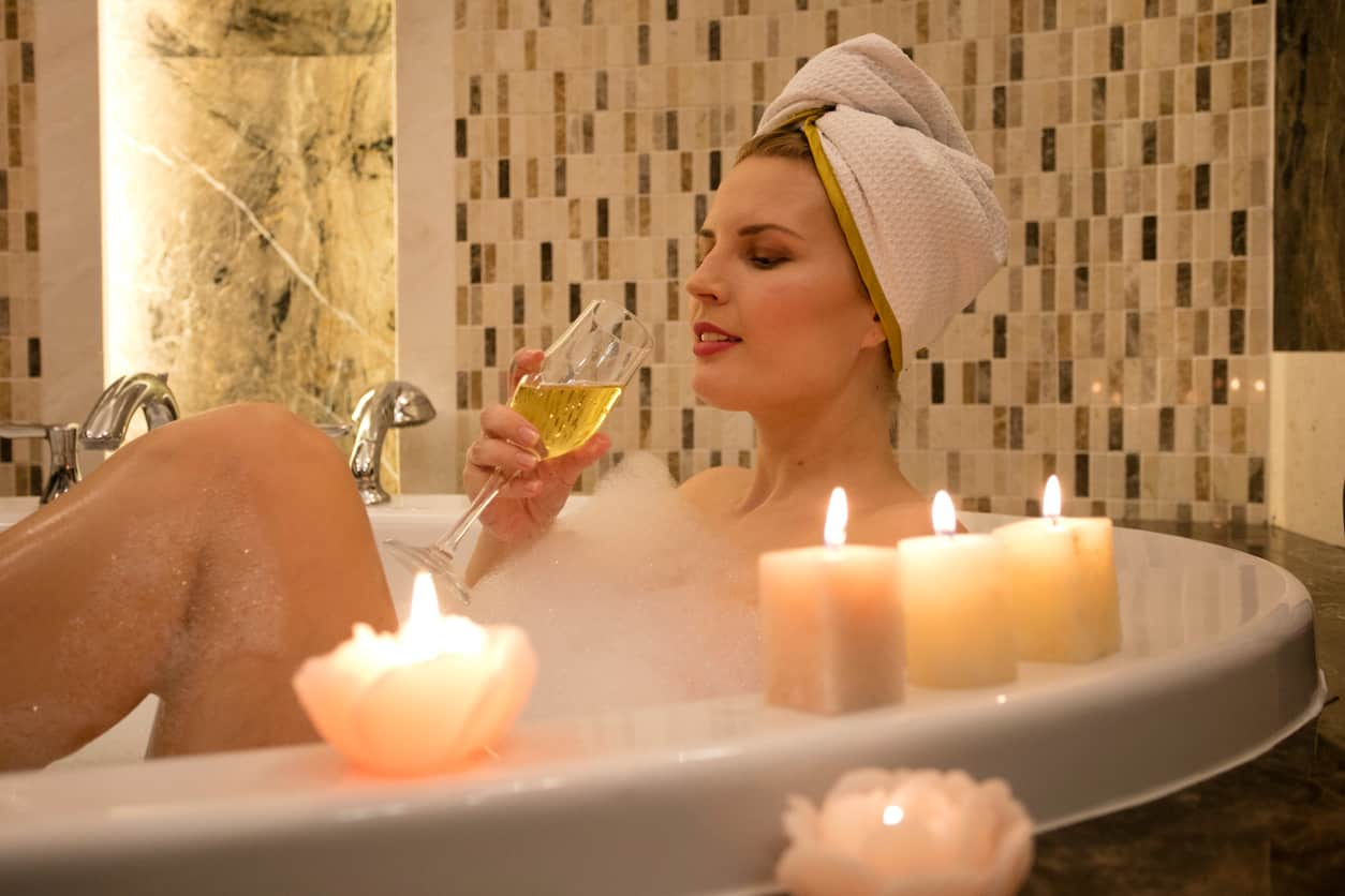 Womn in bubble bath with candles and champagne