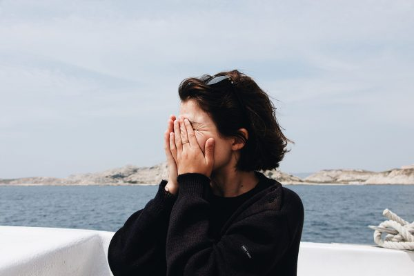 Upset Woman with hands over face standing near the sea