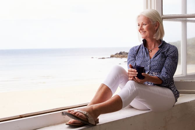 Mature blond woman sitting in window overlooking the sea