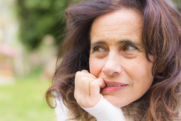 Attractive middle aged woman in the park pondering about life
