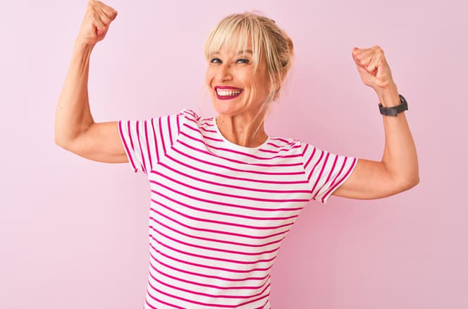 Positive midlife woman with striped shirt showing arm muscles