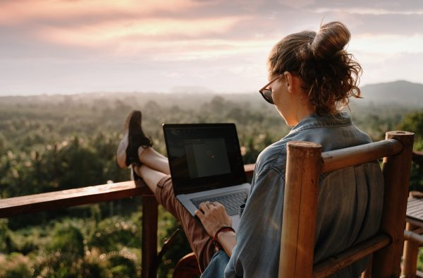 Woman freelancing in exotic location with laptop