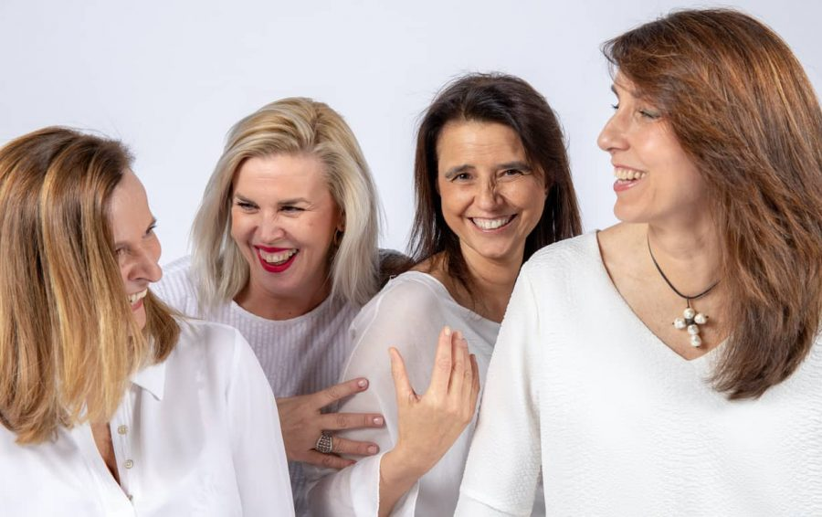 4 middle-aged women over 50 laughing together