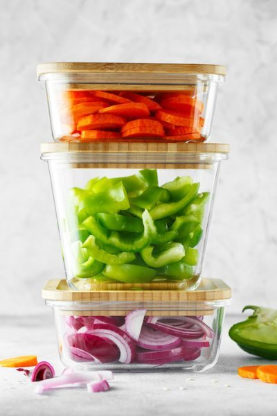 Glass storage containers full of chopped vegetables for refrigerator