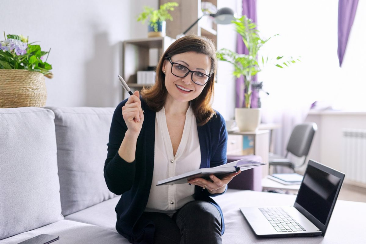 Attractive woman Health Coach in her home sitting looking at camera with laptop, pen and notebook