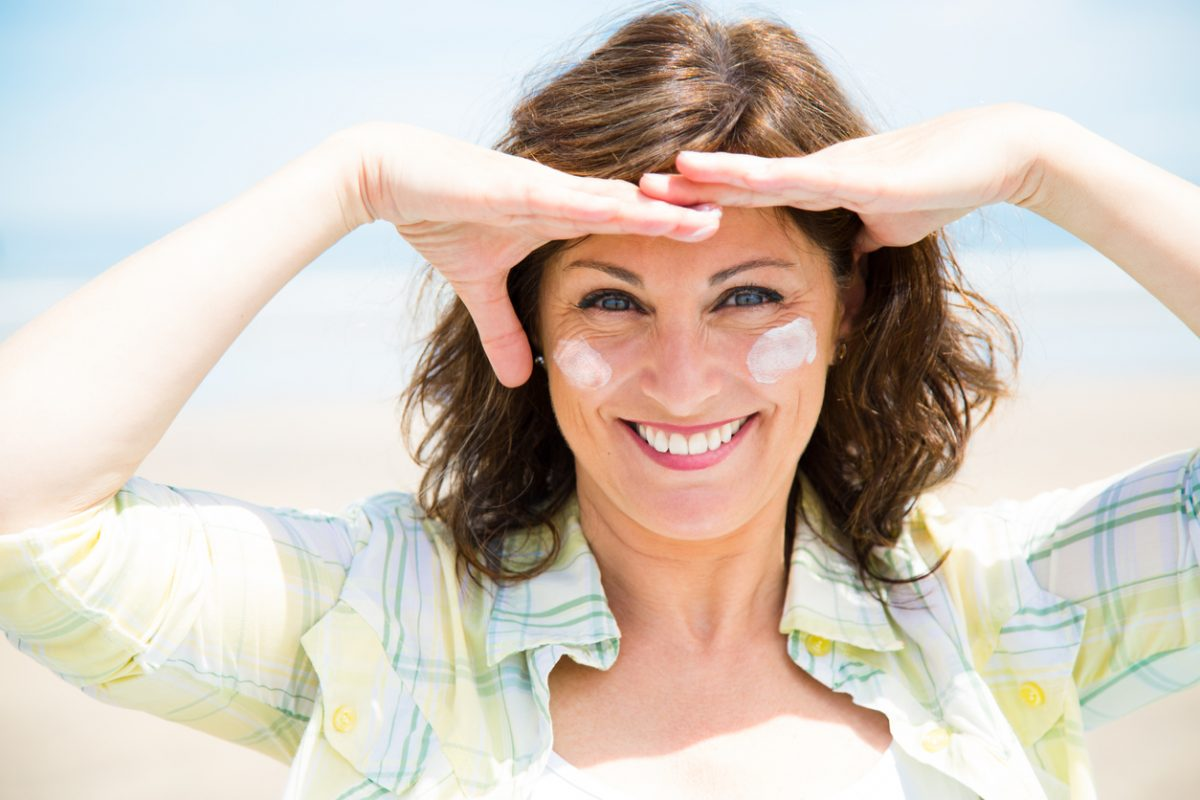 Attractive midlife woman smiling and shielding eyes from the sun