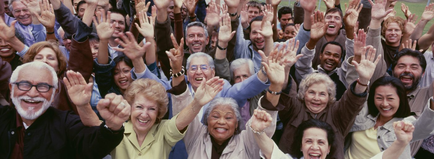 Large group of multi racial people waving at the camera