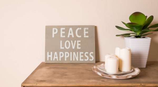 Peace, Love, Happiness printed in tile on a side table with candles
