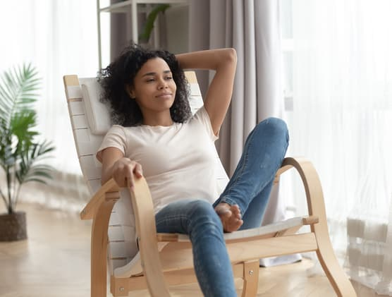 Attractive African woman relaxing in chair taking a break from technology