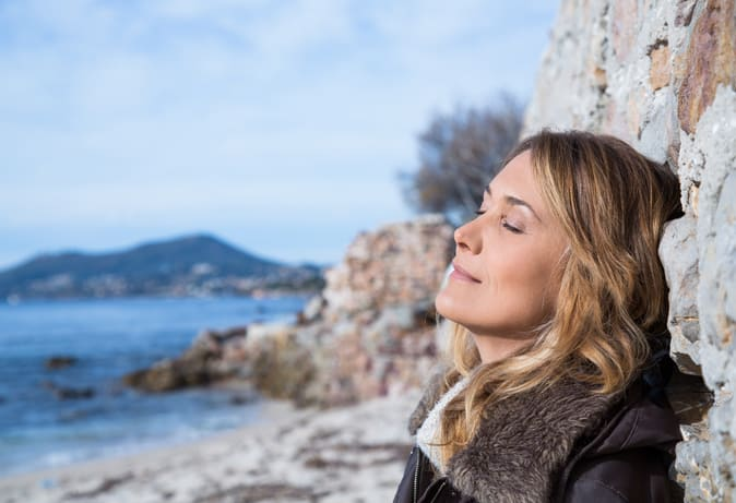 Woman leaning on rocks at the beach with eyes closed enjoying the sunshine