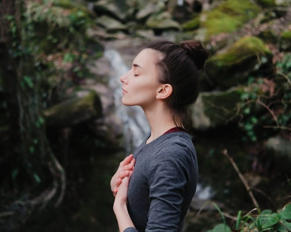 Young woman feeling her spirituality in nature hands on chest and eyes closed