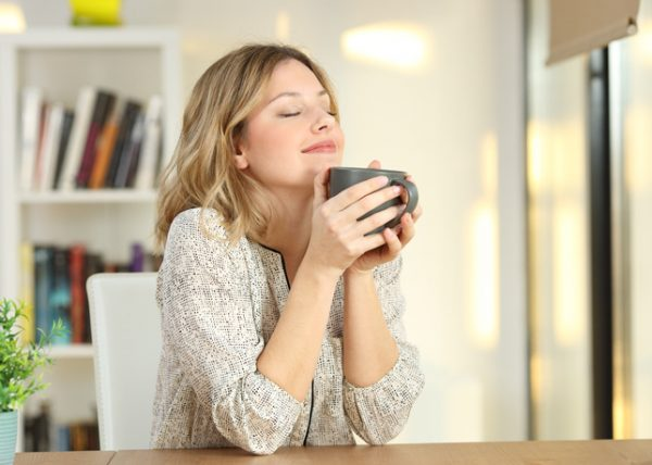 Woman with eyes closed focussed on enjoying her cup of tea