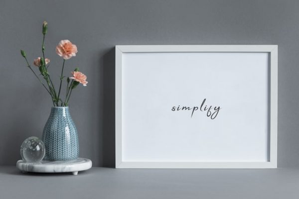 Simplify written on white framed mockup with flowers