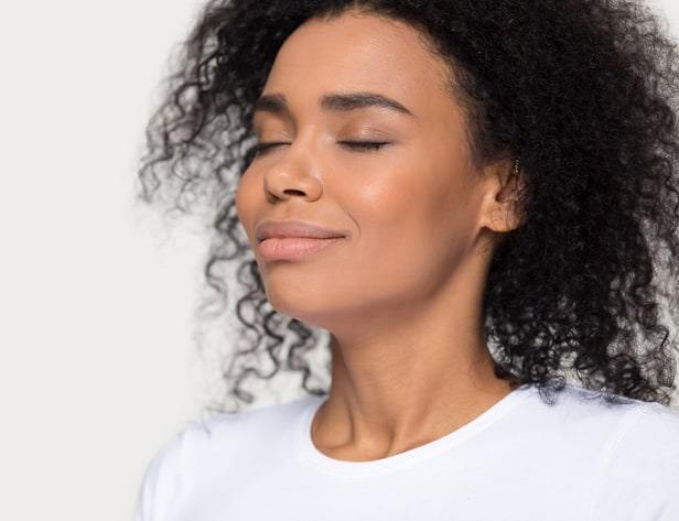 Calm peaceful African American woman with eyes closed breathing deep