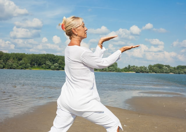 Mature woman in white clothing practicing Tai Chi on the beach