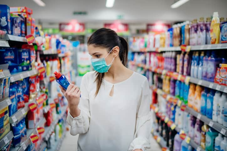 Woman wearing mask looking at cleaning products in a store