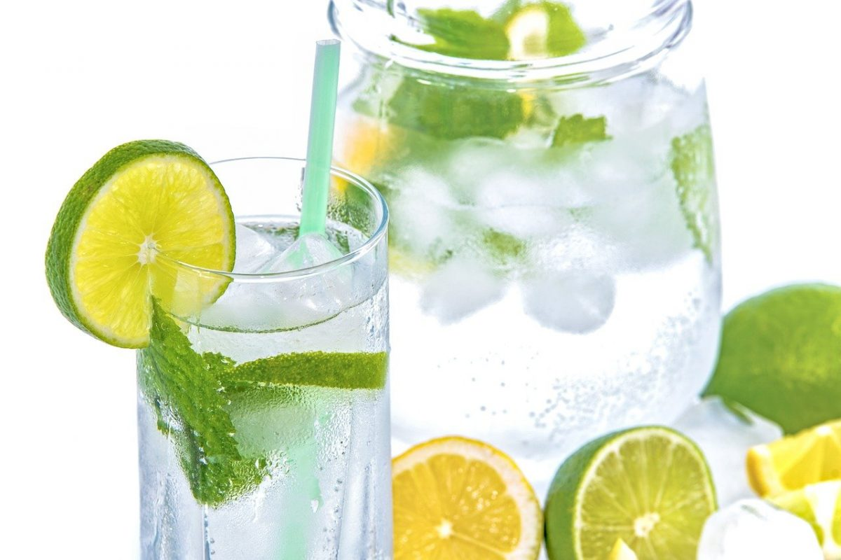 Icy cold mineral water with lemon slices in glass