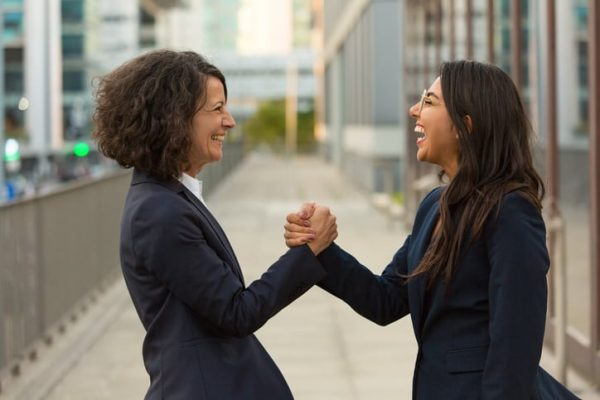 2 female work friends laughing and gripping hands