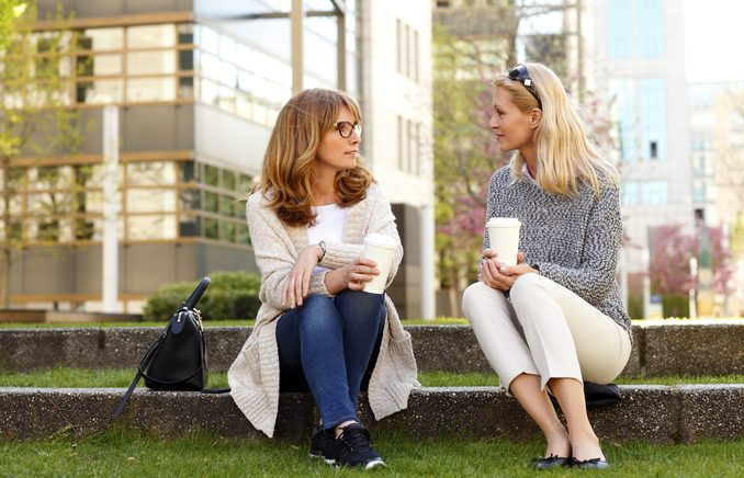 2 middle aged female friends sitting chatting outdoors holding coffees