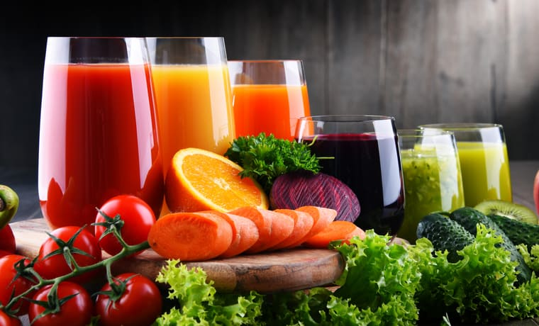 Various glasses of different juices and vegetables