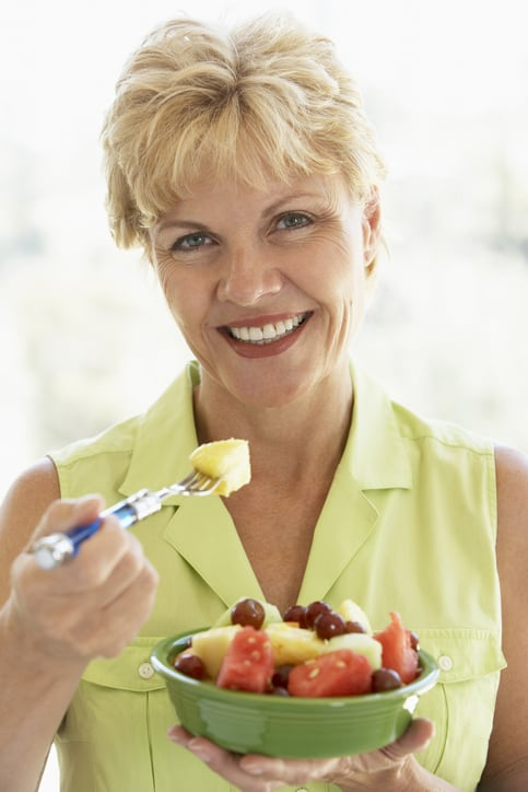 Pretty blond Middle Aged Woman Eating Fresh Fruit Salad