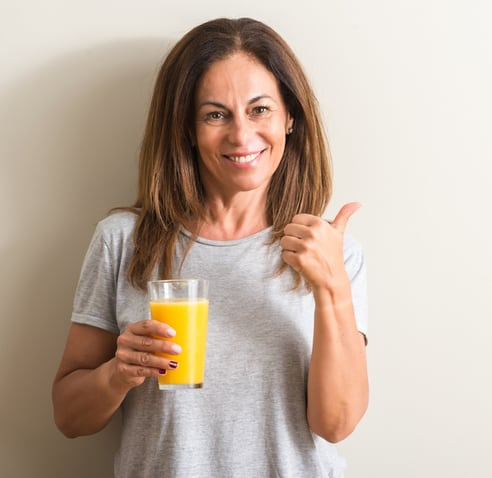 Attractive midlife woman drinking morning juice giving it a thumbs up sign