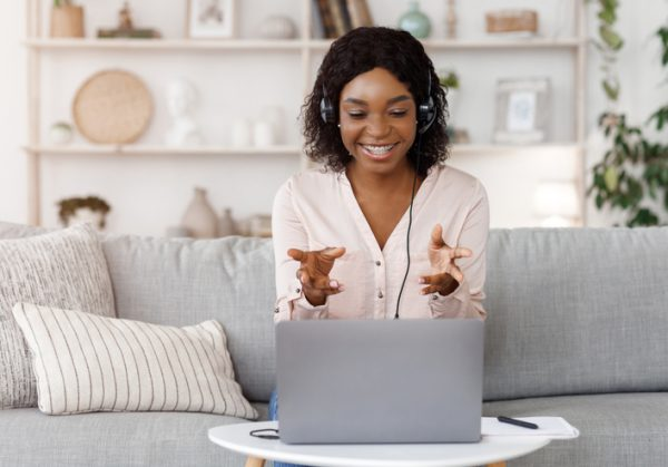 Smiling African American woman with laptop coaching a client online