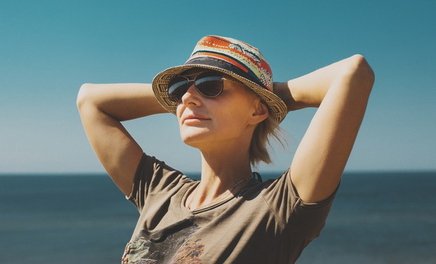 Happy mature woman at beach with hat and sunglasses