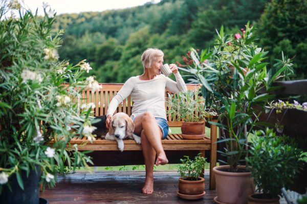 Mature woman sitting in her country garden with her dog