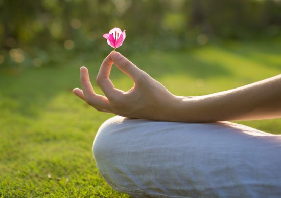 Woman meditating in nature holding a flower petal