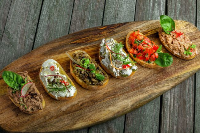 Italian Bruschetta with assorted toppings on wooden board