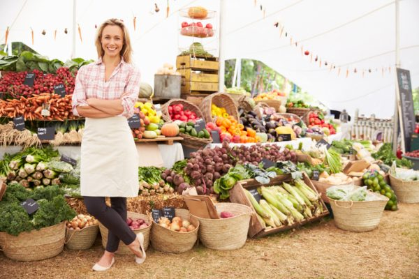 Large fresh food farmer's market with healthy stall holder smiling to camera