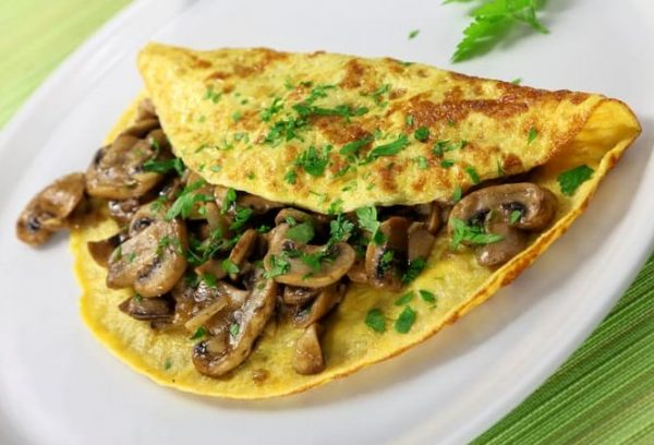 Mushroom & fresh herb omelet on white plate