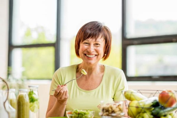 Portrait of a beautiful, healthy mature woman eating fresh salad on the table indoors with window background