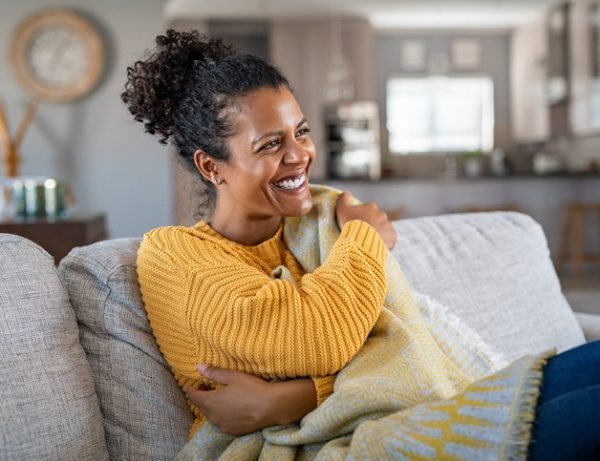 Joyful african woman with blanket on couch laughing
