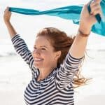 Joyful midlife woman at the beach holding a blue scarf in the wind