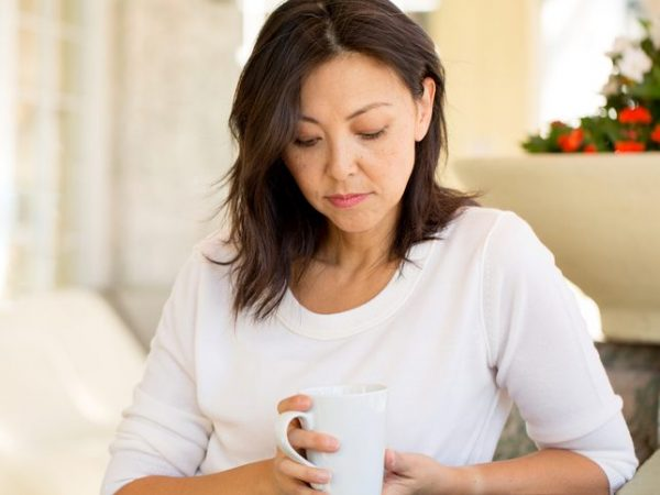 Pretty mature woman in deep thought with coffee