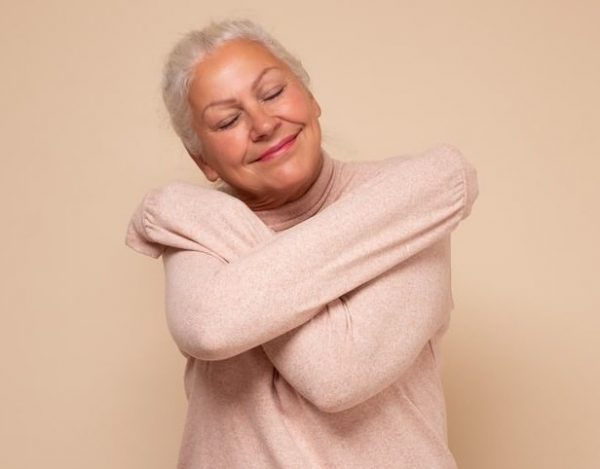 Positive relaxed senior woman closing eyes with pleasure, keeping arms around herself in pink jumper