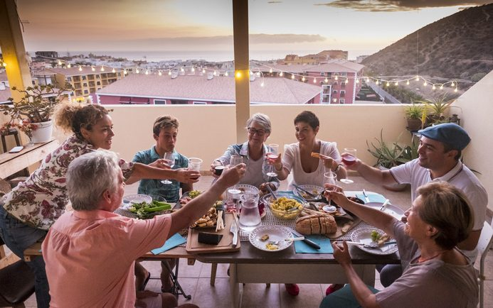 Mediterranean family gathering to share a meal on a terrace with the ocean in the background