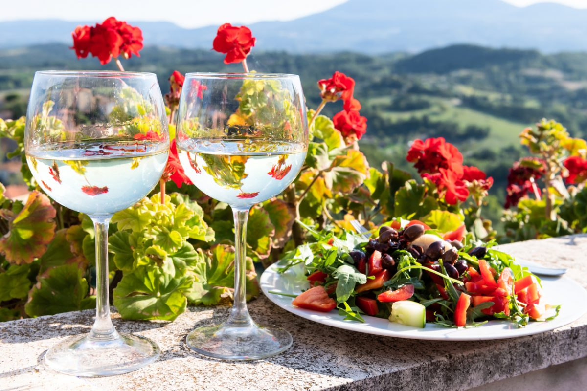 Closeup of arugula salad with olives and white wine two glasses on balcony terrace by red geranium flowers overlooking Tuscan countryside