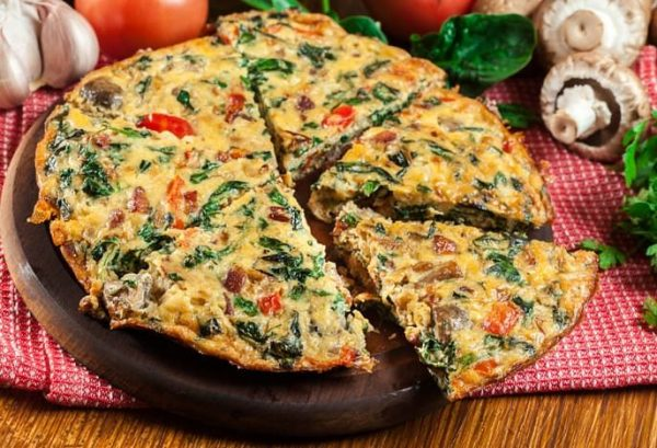 Egg frittata with spinach, mushroom & tomato on wooden board