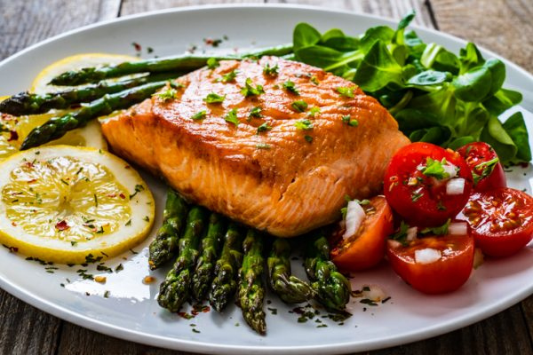 Fried salmon steak and asparagus with cherry tomatoes
