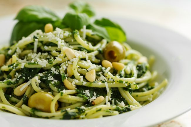 Tasty Beautiful Pasta Closeup with Spinach, Cheese, Olives, Basil and Nuts.