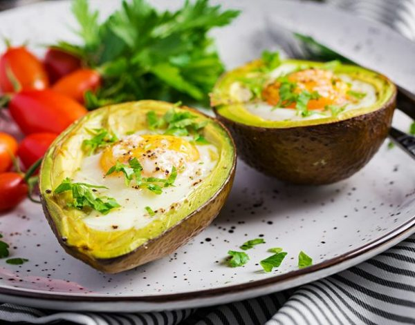 Avocado baked with egg and fresh salad.