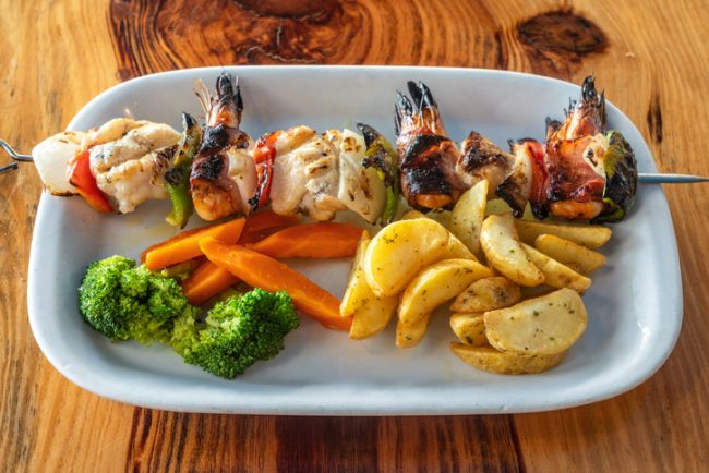 Grilled seafood skewer made of shrimps, fish and peppers with chips, carrots and broccoli on the side shown on white plate